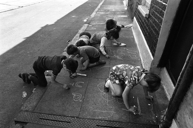 Small children drawing pro Irish Republican Army notes with chalk on the pavement, such as Up the IRA, in Lecson Street in Belfast, Northern Ireland on August 17, 1971. (AP Photo/Peter Kemp)