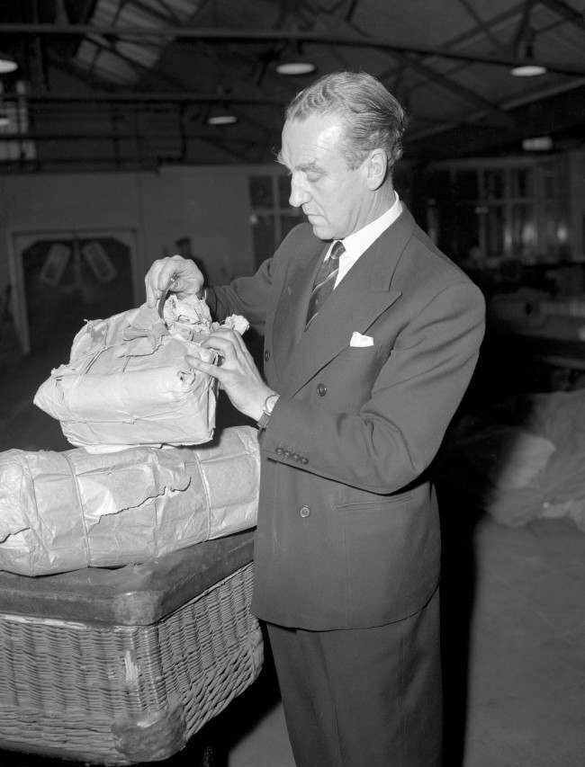 A damaged parcel destined for Cyprus is examined by Postmaster General, Ernest Marples, at the Army's Home Postal Depot at North Acton, London. The PMG was seeing damaged parcels being repaired at the depot, which he was visiting to watch Christmas mail being sorted for Forces overseas Date: 12/12/1958