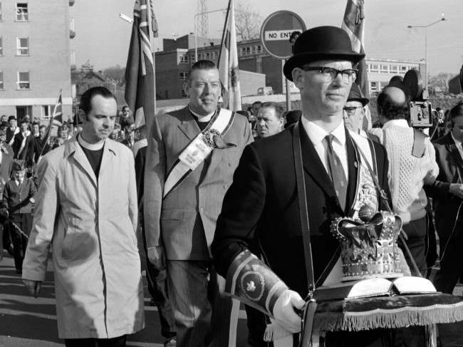 Protestant leader Reverend Ian Paisley, behind crown bearer, leads the Protestant Easter March through Armagh, Northern Ireland, while British troops stand guard on Easter Saturday, April 10, 1971.