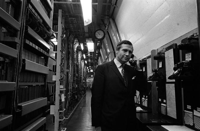 "From 150 ft below Manchester's city centre, Mr John Stonehouse, the Postmaster General, makes a call from the deep level telephone exchange. The exchange was designed ""to protect against total interruption of the telephone trunk service in severe emergency"". * Mr Stonehouse took the opportunity to visit the deep-level exchange while in Manchester to open the new Rutherford trunk exchange which is situated above ground. Date: 07/10/1968"