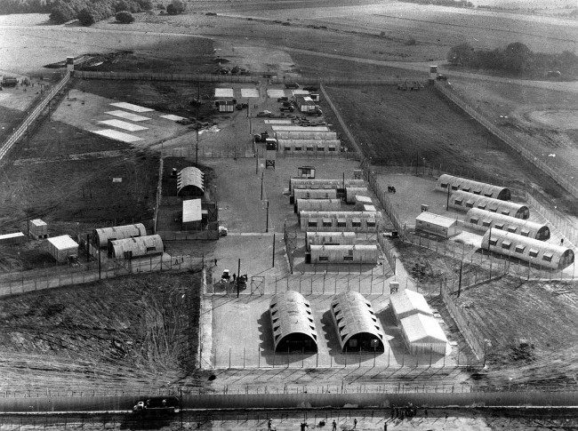 This former airfield is now the internment camp for IRA detainees. The hutments now have central heating and other modern amenities. The camp is called Long Kesh. The airfield was built 30 years ago and used by bombers taking off for Germany. *