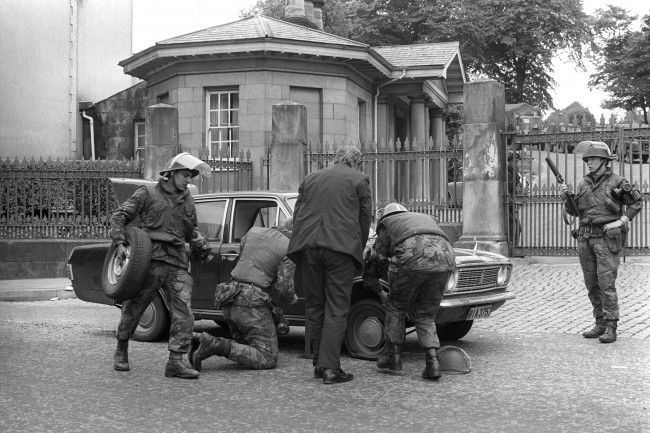 Soldiers changing a flat tyre on a car outside an Army base in Londonderry.