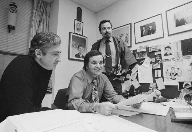 "In this 1972 file photo, ""Mad"" magazine Editor Al Feldstein, center, sits with Art Director John Putnam, left, and a freelancer named Jack, at the magazine's New York headquarters. Feldstein, whose 28 years at the helm of Mad transformed the satirical magazine into a pop culture institution, died Tuesday, April 29, 2014. He was 88. (AP Photo/Jerry Mosey, File)"
