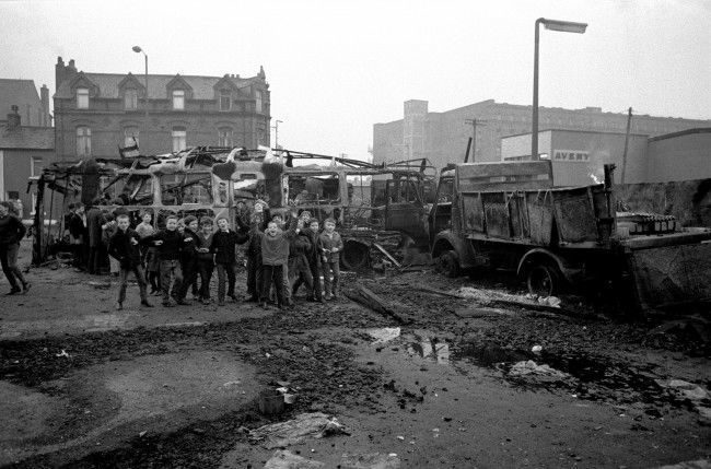Schoolboys cheer adn chant from a pile of burnt-out busses and lorries in the aftermath of the riots. Date: 09/02/1971
