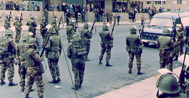 BELFAST IRA CLASHES - British troops straddle a main road near the Catholic Unity flats in Belfast, Northern Ireland, during a lull in the recent current wave of disorders which had flared up in a show of strength by a breakaway group of the Irish Republican Army earlier in the week. Club wielding republican extremists had forcefully halted traffic during the funerals of catholic riot victims. (AP-Photo/Peter Kemp) 02/11/1971