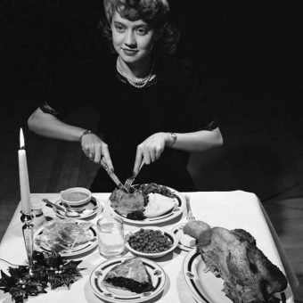 December 1942: Miss Virginia Hammel of McLeod County, Minn. Tucks Into The Typical American Christmas Dinner