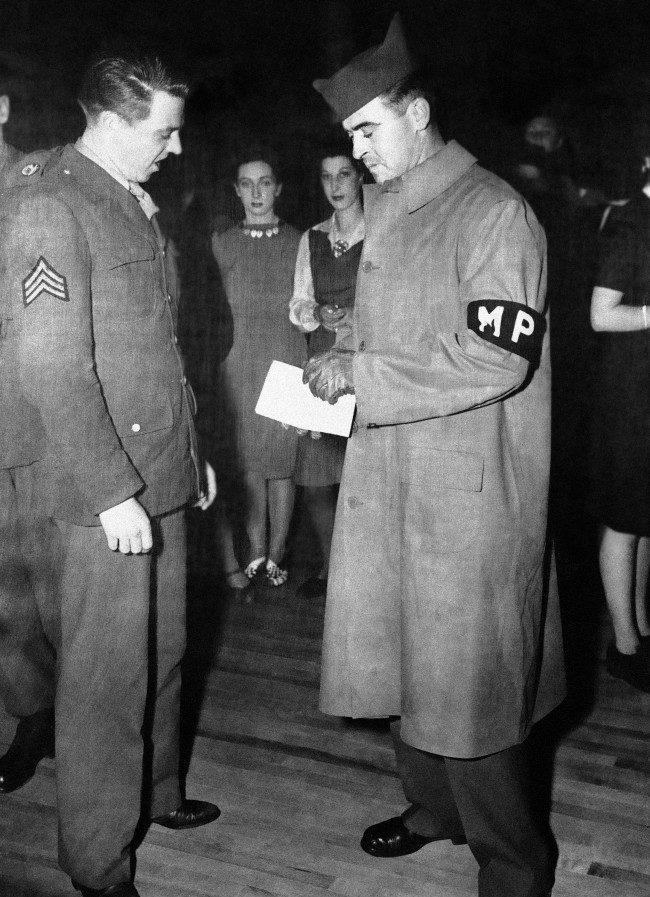 ritish and American civil and military policemen and women, in a sudden widespread check, combed the West End district of London, in a surprise survey calling for identity cards and leave permits on June 2, 1944. As D-Day and H-Hour loom, authorities are on constant alert against any relaxation of home front vigilance. In a dance hall, a U.S. Military policeman checks the leave pass of a U.S. Army sergeant. (AP Photo)