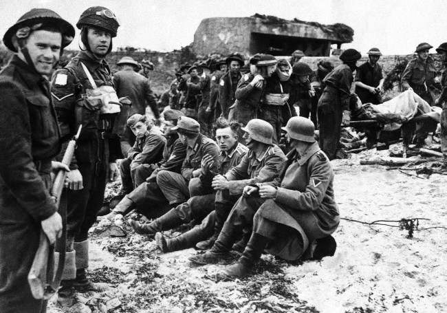Canadian invasion troops stand guard over the first German prisoners captured during the assault on France by Allied forces on June 6, 1944 along a 100 mile front on the Normandy coast between LeHavre and Cherbourg. Wounded soldiers are being treated, in the background. At extreme bear are German coastal fortifications of masonry, silenced by the invaders. (AP Photo)