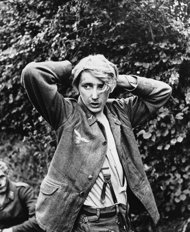Without a shirt and with underwear and coat unbuttoned, a young German soldier captured by Allied forces at St. George D'elle in Normandy looks furtively around on March 28, 1944. (AP Photo)