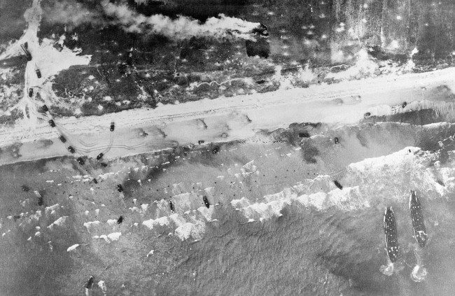 - In this June 6, 1944 file picture, Allied troops come ashore in the surf and vehicles start inland on the German-held beach of Normandy, France during World War II. (AP Photo)