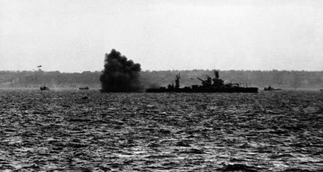 A puff of black smoke blows away from the guns of the USS Arkansas in June 1944 as the might battleship lays down a tremendous barrage against German installations on the beach area of France, in support to the Allied ground forces who stormed the Normandy beaches. (AP Photo)