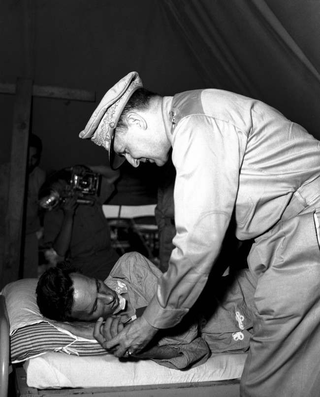 "General Douglas MacArthur leans sympathetically over the hospital bed of Vern Haugland, war correspondent of the Associated Press who fought his way out of the New Guinea jungle after being lost for 43 days. General MacArthur awarded Haugland the Silver Star as a symbol of his ""devotion and fortitude"" when he visited the 34-year-old Associated Press correspondent somewhere in New Guinea on Oct. 3, 1942. (AP Photo/Pool)"