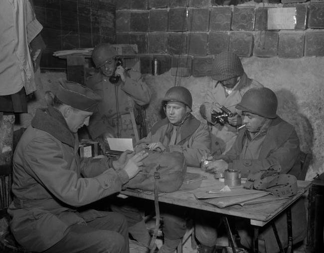 Hal Boyle (center, at typewriter), Associated Press war correspondent, writes a dispatch on North African fighting while Harrison Roberts (second from right), Associated Press photographer, removes film from his camera in an improvised bomb proof field headquarters in North Africa on April 1, 1943. Lt. Joseph E. Schmidt (left foreground), public relations officer, of Harrisburg, Pa., puts copy into a dispatch bag and Capt. Jay R. Vessels (left rear), of Minneapolis, Minn., who is on military leave from the Associated Press, checks air transport command on a field phone. Irving Smith (right) prepares caption material for his film. (AP Photo/Harrison Roberts)