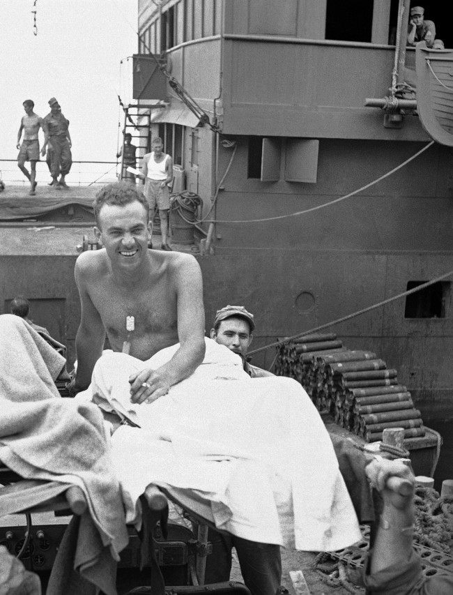Grinning cheerfully as he sits on his litter on the dock at a New Guinea base on August 5, 1943, William F. Boni of New York, Associated Press War Correspondent, heads for treatment of mine shell splinter wounds received on July 9 when a barge on which he was leaving Nassau Bay was strafed by Japanese planes. On August 5 it was announced that he had been given the Purple Heart Medal. (AP Photo)