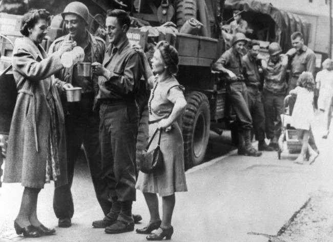 British women pour a mess tin of tea for men from an American convoy heading for the south coast of England during the build-up to the Normandy Landings (D-Day) of June 1944. A small girl chats to other soldiers in the background. Picture part of PA Second World War collection.