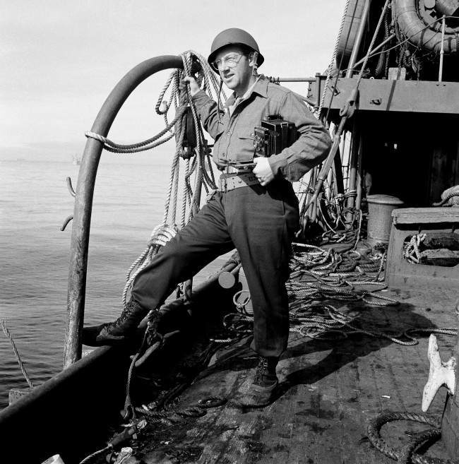 Grant MacDonald, Associated Press war photographer, formerly of the Seattle, Wash. bureau, stands on the deck of a troop transport bound for Kiska, Sept. 4, 1943, accompanied the U.S. and Canadian forces that landed on the Aleutian island on August 16. (AP Photo)
