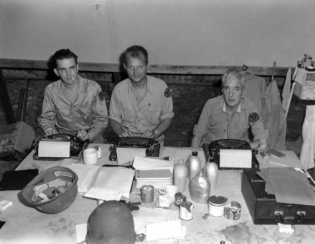 Three war correspondents work in the press hut on Guadalcanal, Nov. 3, 1943. Left to right: Art Burgess, Associated Press; Leif Erickson, Associated Press and Pat Robinson, INS. (AP Photo/Allan Jackson) Ref #: PA.11827193  Date: 03/11/1943