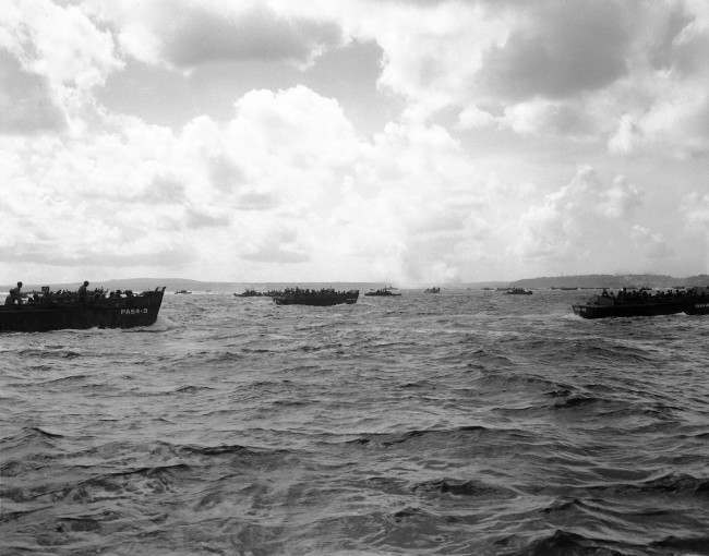 Smoke from Agana torpedo bomber targets are seen in the distance as landing craft race toward the Asan shore at Guam on D-Day, June 6, 1944. (AP Photo/Joe Rosenthal)