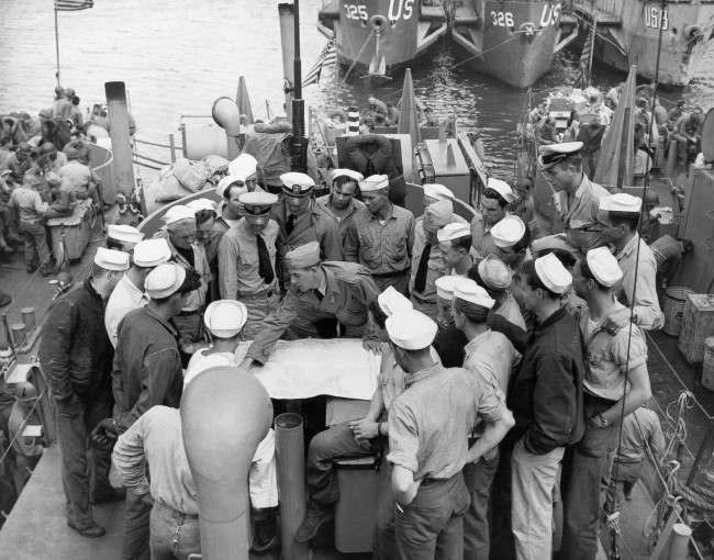 Lt. William V. Patten, centre of group, wearing overseas cap, briefs his crew at a port in England before the invasion of France began June 6, 1944. Patten and his ship are veterans of Tunisia, Salerno, Anzio and Licata. (AP Photo)