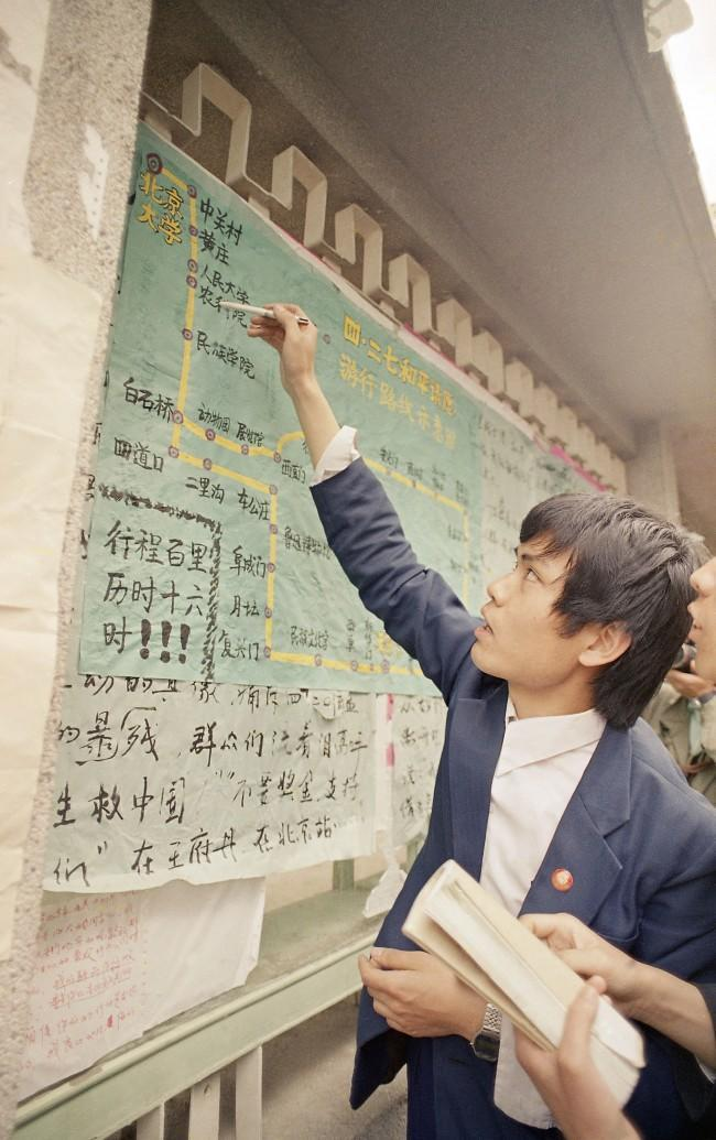 A student at Beijing University points to a map of the march route on a poster up on campus as he recounts a tale of how marchers pushed through police lines on their way to Tiananmen Square, April 28, 1989. (AP Photo/Mark Avery)