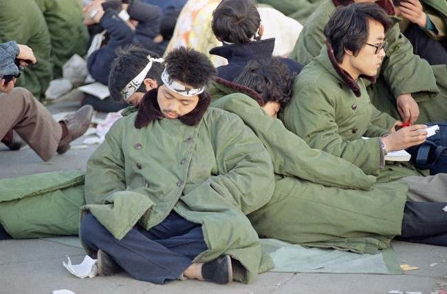 Student protesters in Beijing's Tiananmen Square sleep leaning on one another at sunrise, Sunday, May 14, 1989 in Beijing. The protesters, some of them on a hunger strike, plan to remain in the square for the official welcoming ceremony for Soviet leader Mikhail Gorbachev on Monday. (AP Photo/Mark Avery)