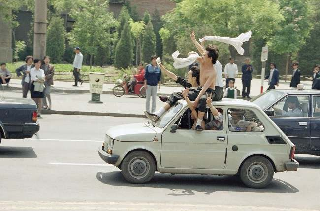 Beijing youths ride atop a car as they parade to Tiananmen Square for a freedom rally, Wednesday, May 17, 1989 in Beijing. (AP Photo/Sadayuki Mikami)