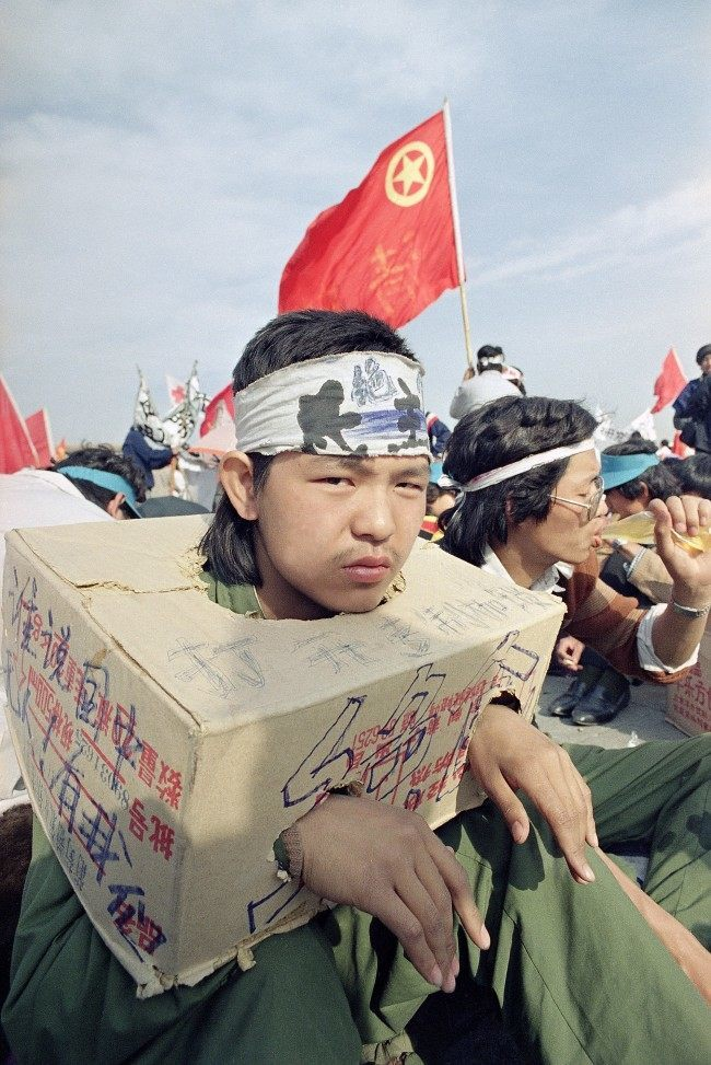 A Beijing university student sits bound in a cardboard box as the strike for democracy continues for the third day in Beijing's Tiananmen Square, Tuesday, May 16, 1989. The box indicates he cannot use his hands so he cannot eat. (AP Photo/Sadayuki Mikami)