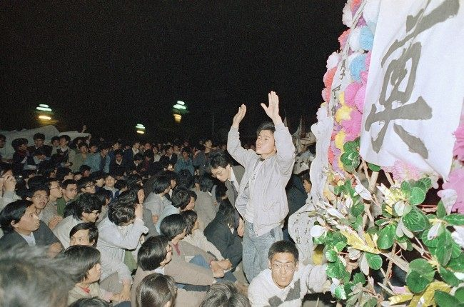 A student leader tries in vain to settle down a crowd of Beijing University students who converged on the Chinese Communist Party headquarters at Zhongnanhai early on Wednesday, April 19, 1989 in Beijing after demonstrating in Tiananmen Square all day on Tuesday. The students later tried to storm the gate, but were fought by Chinese security. (AP Photo/Mark Avery)