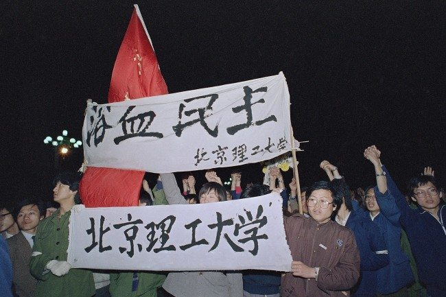 Students from Beijing University of Engineering carry a banner, top, reading 'Democracy, Bathed in Blood,' as they march into Beijing's Tiananmen Square to join tens of thousands of other students early on Saturday, April 22, 1989. The students plan to spend the night in the square and wait for the funeral of Hu Yaobang later in the day. (AP Photo/Mark Avery)