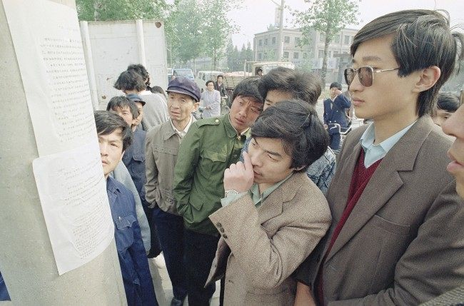 Beijing residents read a copy of a newspaper printed by students and placed on a streetlight pole near the Beijing University campus describing the student demonstrations on Friday and Saturday at Tiananmen Square, April 24, 1989. The student paper, placed on trees and light-posts around the city is an attempt to counter a government imposed news black-out of student demonstrations. (AP Photo/Mark Avery)