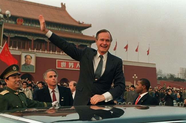 President Bush stands on his car and waves in Tiananmen Square in Beijing during a visit to China in this Feb. 25, 1989 photo. On the wall in the background is a portrait of Mao Tse-tung at the entrance to the Forbidden City. Now that the elder Bush's son is about to become President George W. Bush, the Chinese are uneasy. While campaigning, George W. Bush and his foreign policy advisers asserted U.S. interests in ways China finds threatening. (AP Photo/Doug Mills, File)