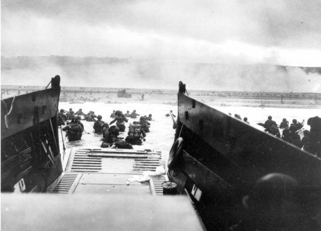 Under heavy German machine gun fire, American infantrymen wade ashore off the ramp of a Coast Guard landing craft on June 6, 1944, during the invasion of the French coast of Normandy in World War II.