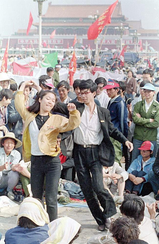 A young unidentified couple, two out of thousands of university students who are holding Tiananmen Square occupied for nine days, pass the time with a lively dance on Monday morning, May 22, 1989 in Beijing, China. (AP Photo/Mark Avery)
