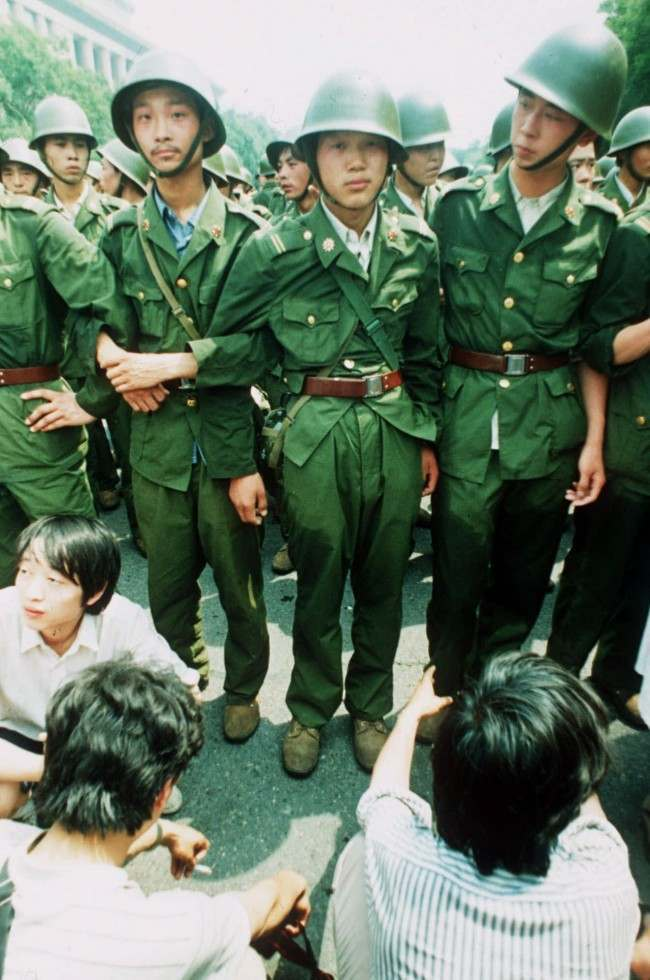 PLA soldiers locked in arms try to march past a human blockade of students outside of the Great Hall of People in this June 3, 1989 photo. Soldiers were reported to resort to teargas and amunitions. On Friday, it will be 10 years since the military assault that killed hundreds and ended seven weeks of protests centered on Tiananmen Square. (AP Photo/Liu Heung Shing)