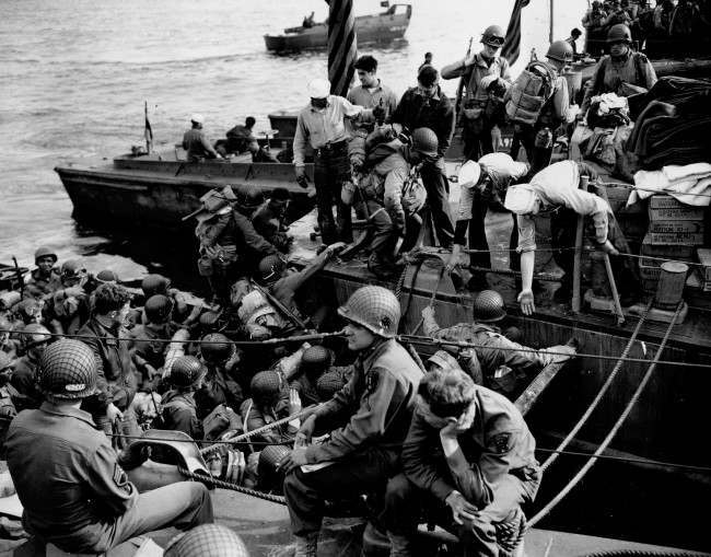 Men and supplies are being ferried out to landing crafts enroute for the initial Allied invasion of the Normandy, June 6, 1944. (AP Photo/Peter Carroll)