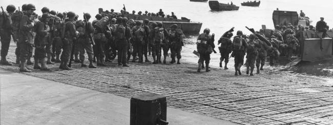 As the Allied invasion of the Normandy gets underway, American troops are shown as they embark in landing crafts at a British port, on June 6, 1944. (AP Photo/Peter Carroll)