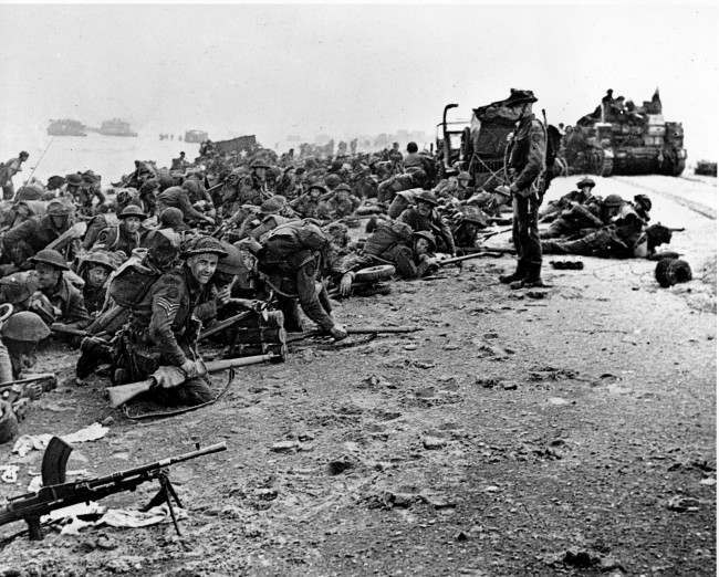 After landing at the shore, these British troops wait for the signal to move forward, during the initial Allied landing operations in Normandy, France, June 6, 1944. (AP Photo)