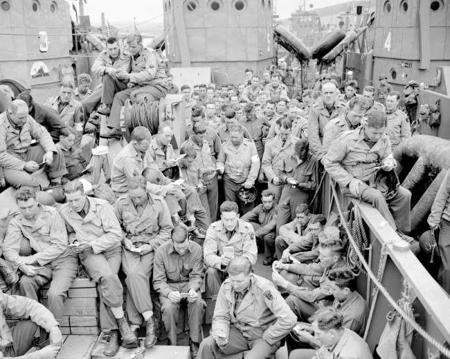 U.S. serviceman attend a Protestant service aboard a landing craft before the D-Day invasion on the coast of France, June 5, 1944. (AP Photo/Pete Carroll)