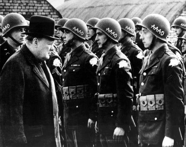 "British Prime Minister Winston Churchill, left, reviews American troops at a base in England on the eve of D-Day, June 1944, during World War II. The initials AAAO on the steel helmets with a line across the As stands for ""Anywhere, Anytime, Anyhow, Bar Nothing."" The identification shoulder patches of the G.I.s are blotted out by the censor. (AP Photo)"
