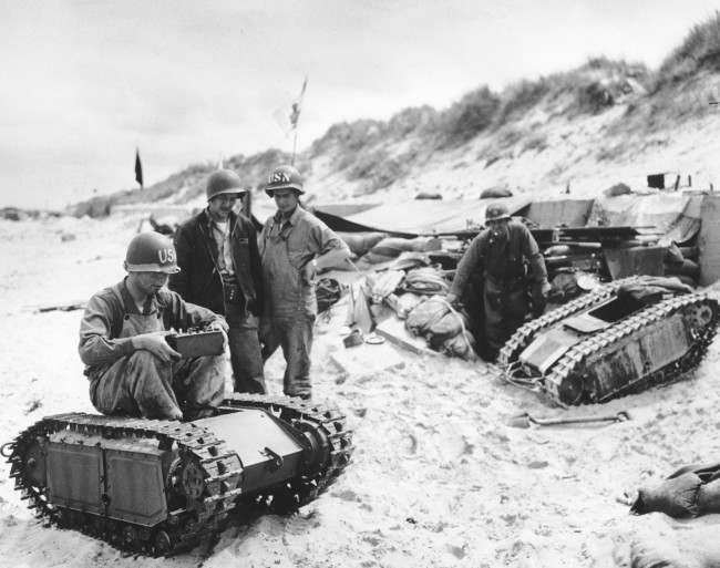 "U.S. Navy men take apart a German ""Beetle"", a miniature tank loaded with explosives, during the Allied Normandy landings in France, in June 1944. (AP Photo)"