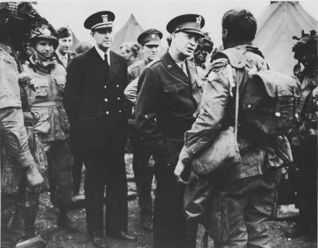 Supreme Commander Dwight Eisenhower visits paratroopers of the 101st Airborne Division at the Royal Air Force base in Greenham Common, England, three hours before the men board their planes to participate in the first assault wave of the invasion of the continent of Europe, June 5, 1944. (AP Photo)