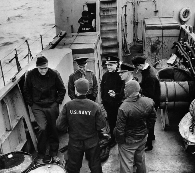 A group of press correspondents chat on board a USS Landing Craft Infantry (LCI) enroute to amphibious maneuvers somewhere off the coast of England on May 8, 1944. With faces to camera, from left: Clark Lee of International News Service; Bill Higginbotham of United Press; Lt. Comm. Barry Bingham, of Louisville, Ky.; Lt. John Mason Brown, New York City; Lt. Byer, with cigarette, Navy ensor. Back to camera: John Moroso, left, of Associated Press; and A.J. Liebling of the New Yorker magazine. (AP Photo)