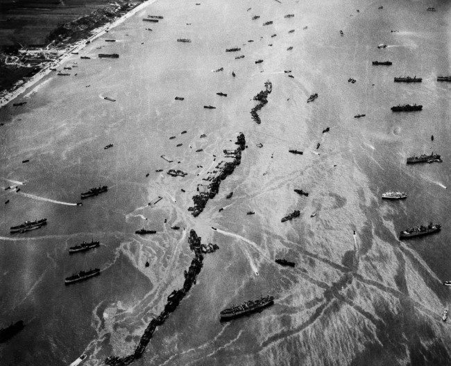Thirteen liberty ships, deliberately scuttled to form a breakwater for invasion vessels landing on the Normandy beachhead lie in line off the beach, shielding the ships in shore. The artificial harbor engineering installation which was prefabricated and towed across the Channel. 1944 photo. (AP Photo)