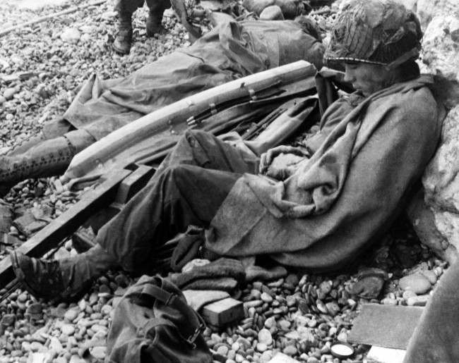 Two American soldiers rest against a chalk cliff on the beach of the Normandy coast of France after landing in June,1944. Man at right is wrapped in blanket and soldier at left stretches out beside an inflatable belt he apparently wore while making his way ashore. (AP Photo)