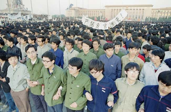 Chinese students link arms in solidarity at dawn on Saturday, April 22, 1989 in Beijing's Tiananmen Square after spending the night there in order to be on hand for memorial services for the late purged party chief Hu Yaobang. The students defied warnings against demonstrating and gathered by the tens of thousands forcing officials to back down and allow them to stay. (AP Photo/Sadayuki Mikami)
