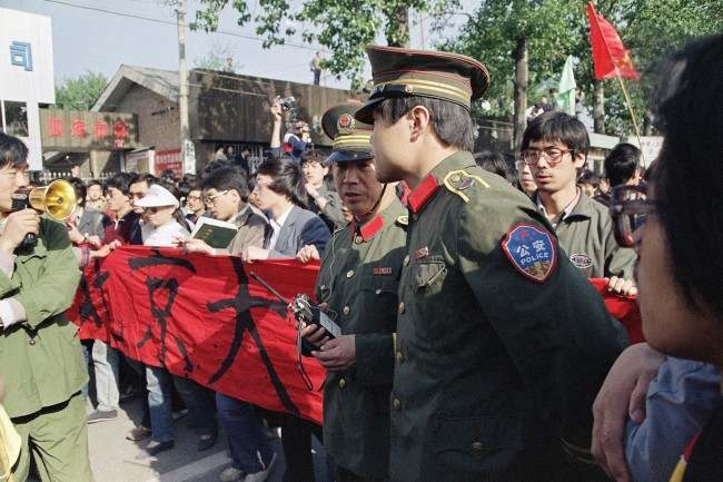 Chinese police try in vain to convince students from Beijing University not to march as they emerged from their campus on Thursday, April 27, 1989 in Beijing. The students from several Beijing universities began a planned march to Tiananmen Square on Thursday in defiance of a government demand they end their campaign for political reform. (AP Photo/Mark Avery)