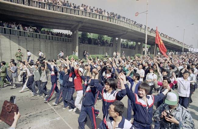 Students of Teachers University raise their hands to appeal to supporting citizens near Tiananmen Square, Thursday, May 4, 1989 in Beijing. (AP Photo/Sadayuki Mikami)