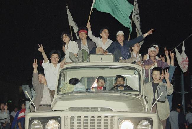 Unidentified demonstrators showing victory signs head to Tiananmen Square, Saturday, May 20, 1989, Beijing, China. (AP Photo/Sadayuki Mikami)