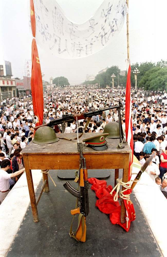 Chinese military items, including rifles, helmets, and a hat, are displayed during the pro-democracy demonstration that lasted from mid-April to early June 1989 on Beijing's Tiananmen Square. The demonstration ended with a government crackdown on June 4, 1989, leaving hundreds dead. (AP Photo/Jeff Widener)