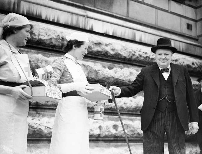 The Prime Minister, Winston Churchill, MP buying a Red Cross flag from a St. John's Ambulance nurse standing next to a Red Cross Nurse on the day the allies launched their invasion of mainland Europe with 'Operation Overlord'